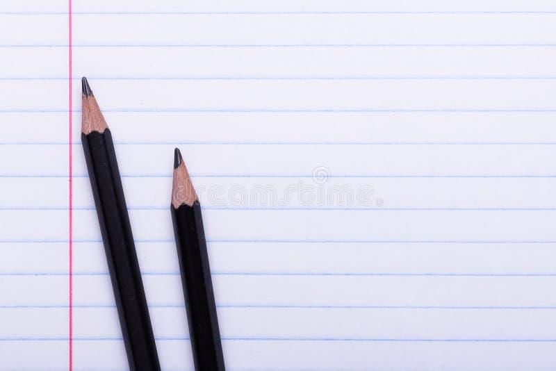 在白色板料的两支黑石墨铅笔在线回到学校的拷贝空间,教育概念 图库摄影