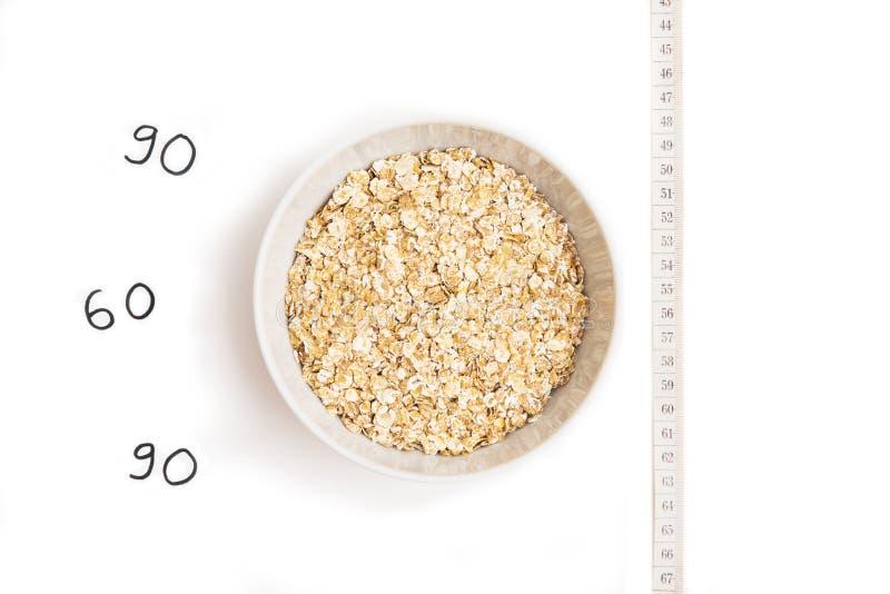 在白色板材、厘米和题字的燕麦粥在白色背景 库存照片
