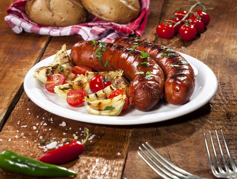 在白色板材和木背景的烤香肠 免版税库存照片