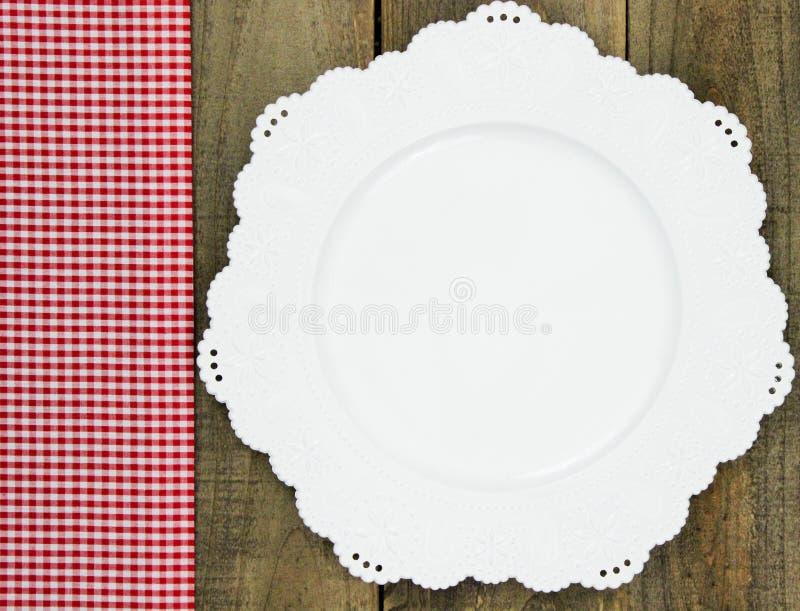 在白色板材旁边的红色方格的织品边界在土气木桌上 库存照片
