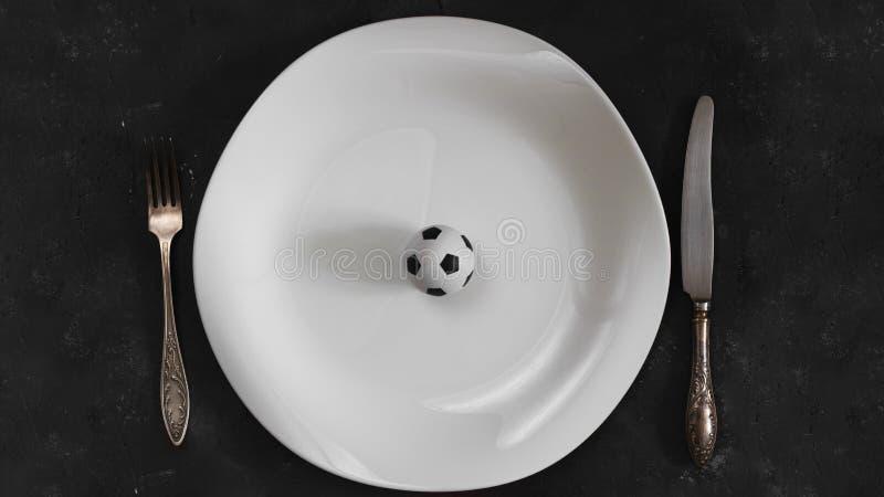 在白色板材有叉子的和刀子的小橄榄球球在织地不很细黑板背景 o 免版税库存照片