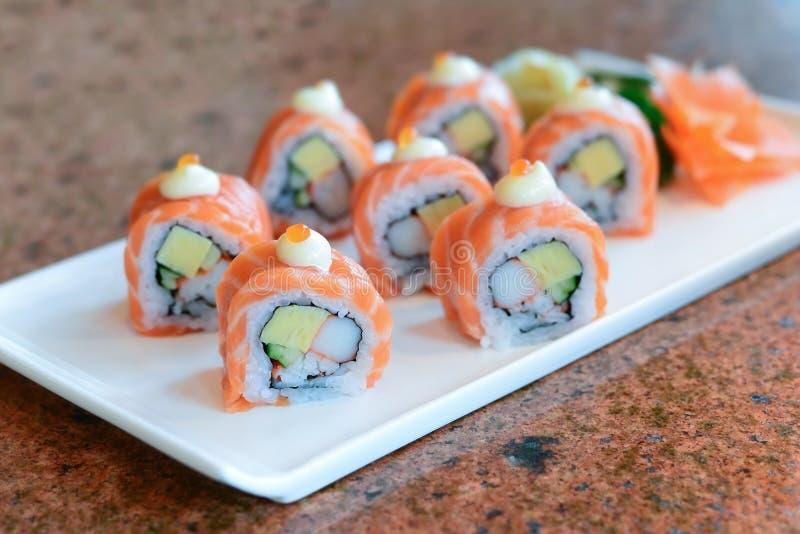 在白色板材服务的三文鱼寿司卷 免版税库存照片