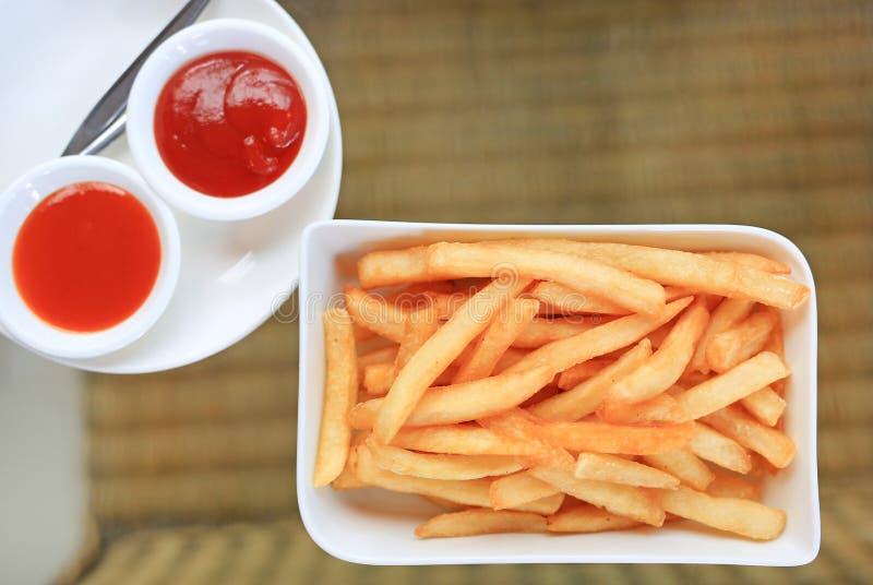 在白色板材服务的薯条用辣椒和西红柿酱在桌上 在蓝色被定调子的工具视图之上 库存图片