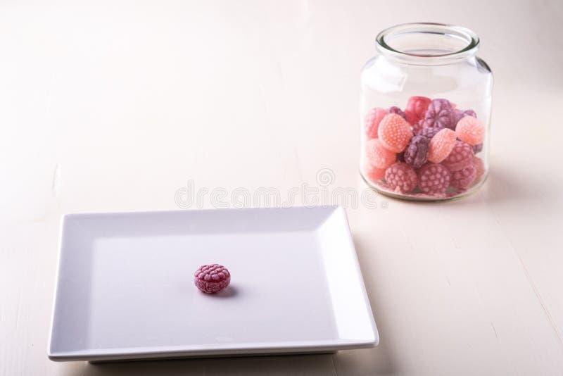 在白色板材的一个棒棒糖有棒棒糖甜点的以水多的莓果的形式在玻璃瓶子的在白色背景 免版税库存照片