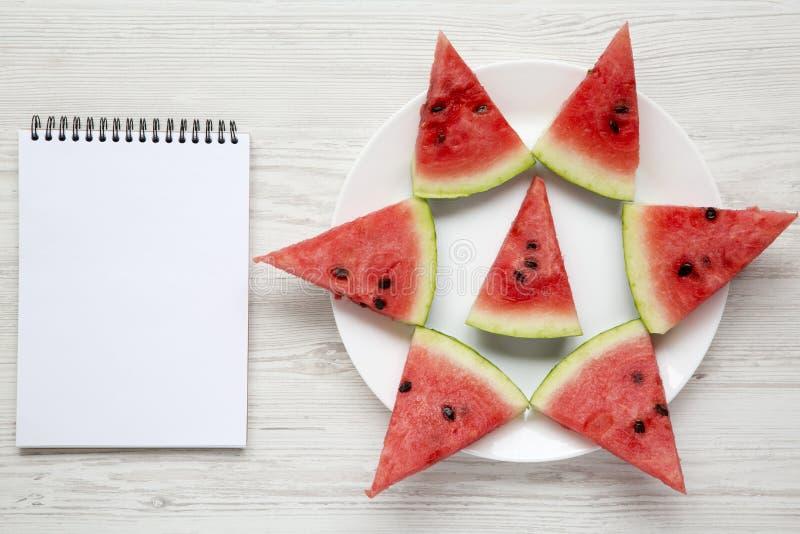 在白色板材的切的西瓜有在白色木背景,顶视图的空白的笔记薄的 库存图片