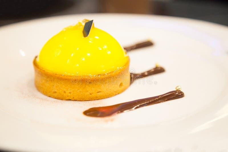 在白色板材的新近地被烘烤的鲜美自创工匠乳蛋糕奶油柠檬馅饼有巧克力装饰的 食品成分,蛋糕,bak 图库摄影