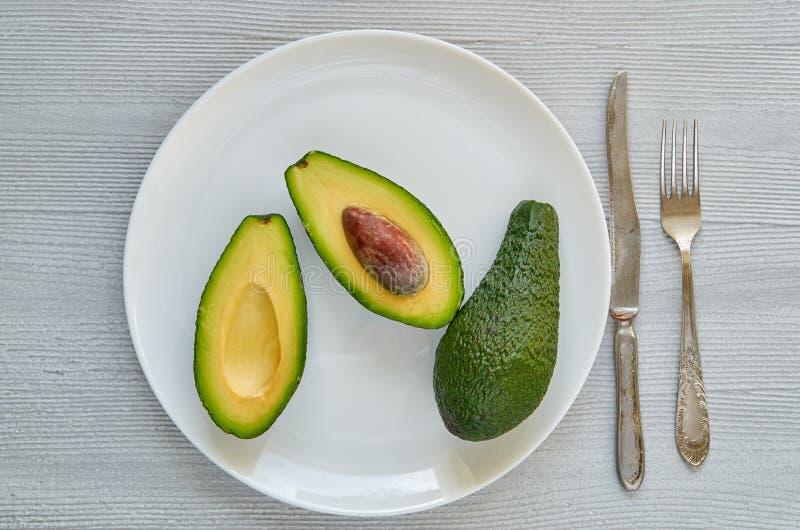 在白色板材的新鲜的切的鲕梨 在灰色背景的健康素食主义者饮食食物 库存照片
