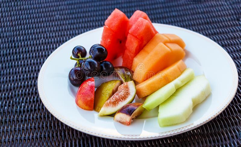 在白色板材的新鲜的有机热带水果 背景 免版税图库摄影