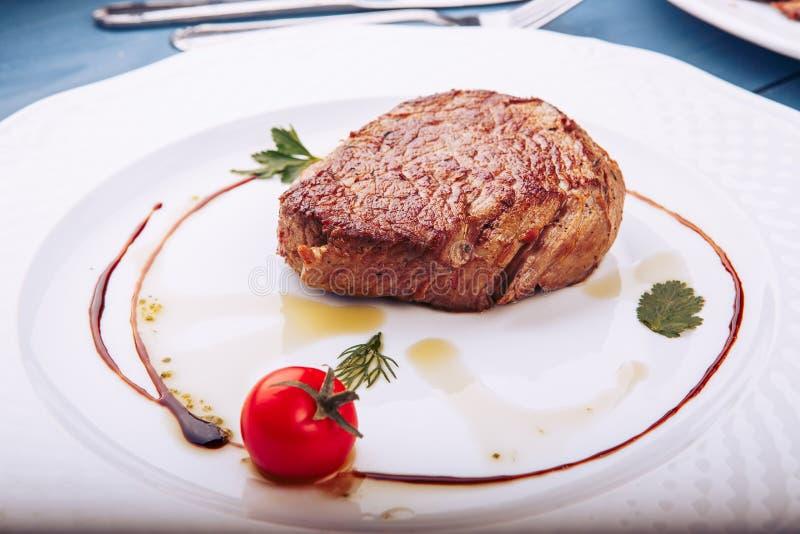 在白色板材的烤丁骨牛排在黑暗的木背景 免版税库存照片