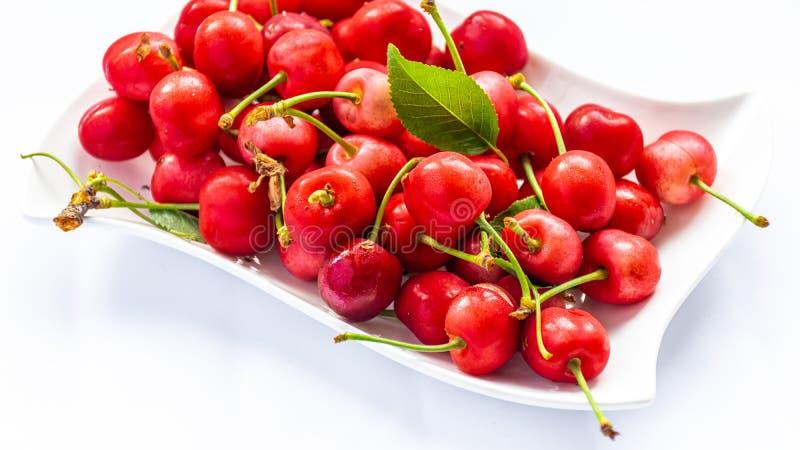 在白色板材的红色樱桃 库存照片