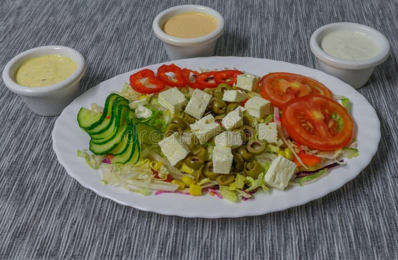 在白色板材的菜沙拉用乳酪和橄榄 免版税库存照片