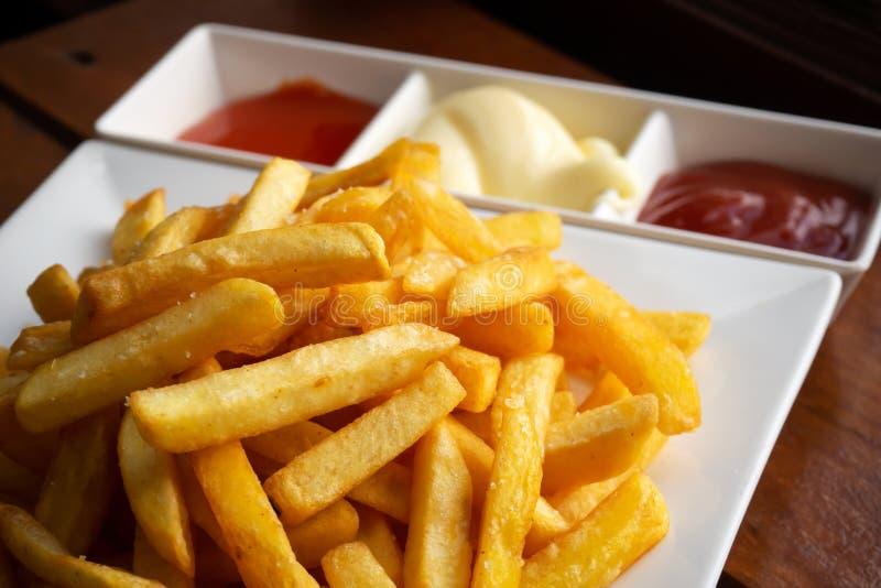 在白色板材的薯条服务用辣椒、西红柿酱和蛋黄酱 美国垃圾食品喜爱的快餐  免版税图库摄影