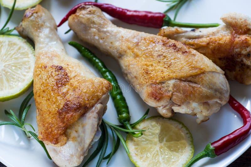 在白色板材的鸡腿有rosemay和石灰的 免版税库存图片