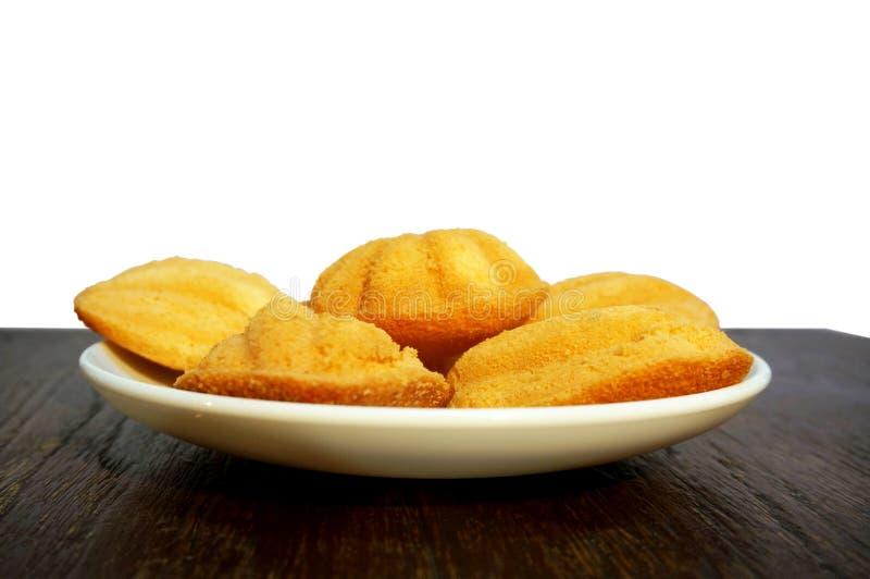 在白色板材的Madeleines曲奇饼在木桌上 库存图片
