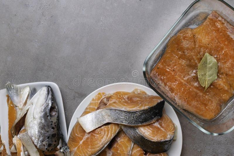 在白色板材,头,在玻璃碗的内圆角的新鲜的未加工的鳟鱼或三文鱼分鱼刀牛排,用在石背景的香料 创造性 库存照片