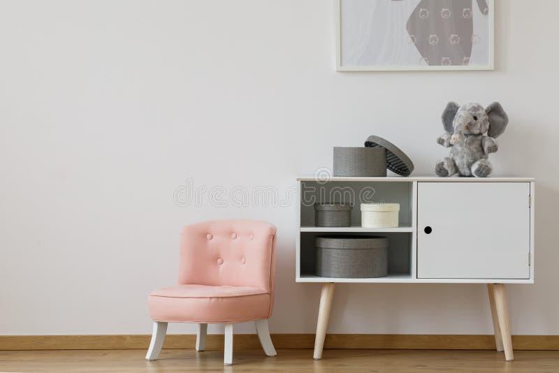 在白色架子旁边的桃红色椅子 库存图片