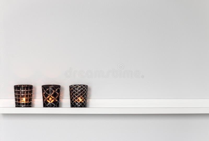 在白色架子的蜡烛光 免版税库存照片