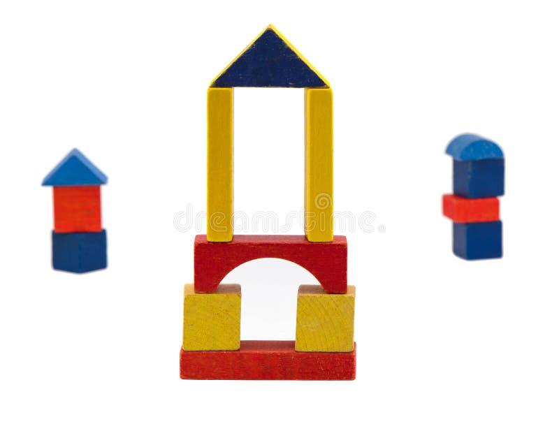 在白色查出的五颜六色的木日志玩具立场 免版税库存照片