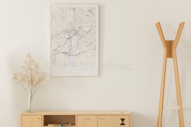 在白色框架,在一个玻璃花瓶的花的地图在木架子,在木挂衣架旁边,真正的照片 库存照片