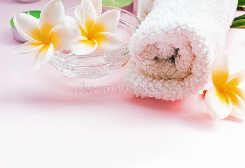 在白色桌上的干净的滚动的毛巾和羽毛花 免版税库存图片