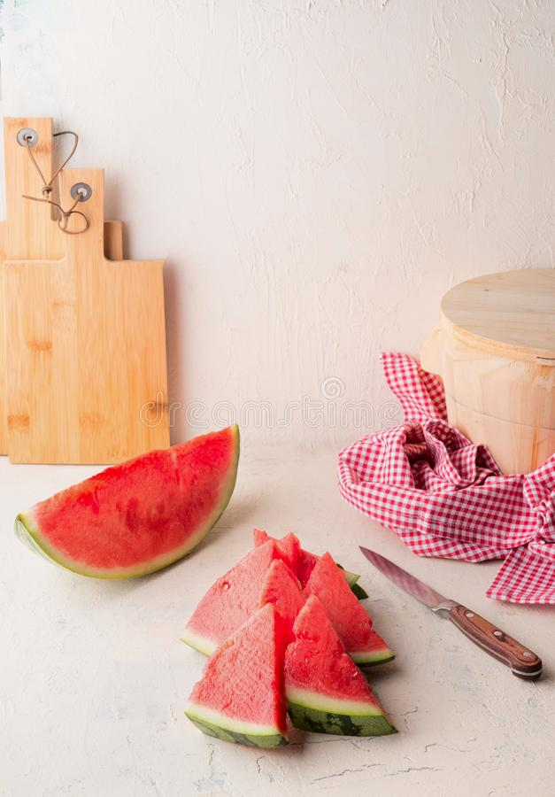 在白色桌上的新鲜的切的西瓜在与刀子的墙壁背景 水多的刷新的夏天食物 r 库存照片