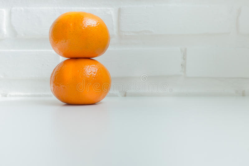 在白色桌上的新鲜的桔子有白色砖背景 免版税库存照片