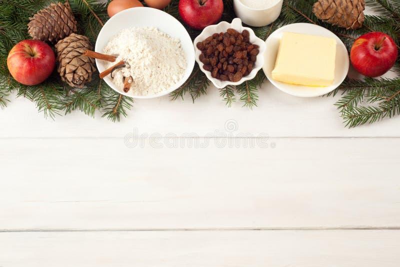 在白色桌上的烘烤成份 鸡蛋、黄油、香料、苹果、葡萄干、香草和肉桂条、白面和xmas树 免版税图库摄影