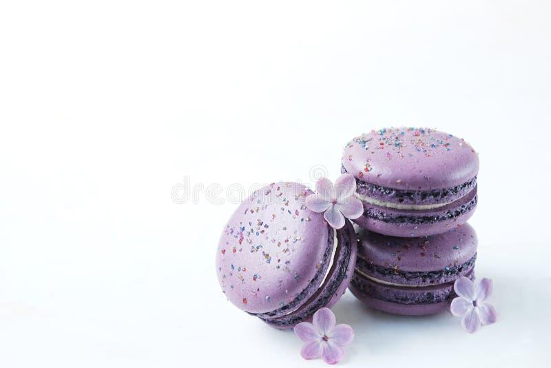 在白色桌上的紫色蛋白杏仁饼干 甜macarons 与拷贝空间的顶视图您的文本的 库存图片