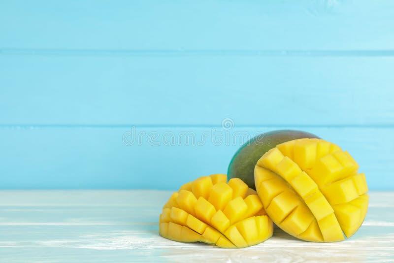 在白色桌上的被切的成熟芒果反对颜色背景 免版税库存图片
