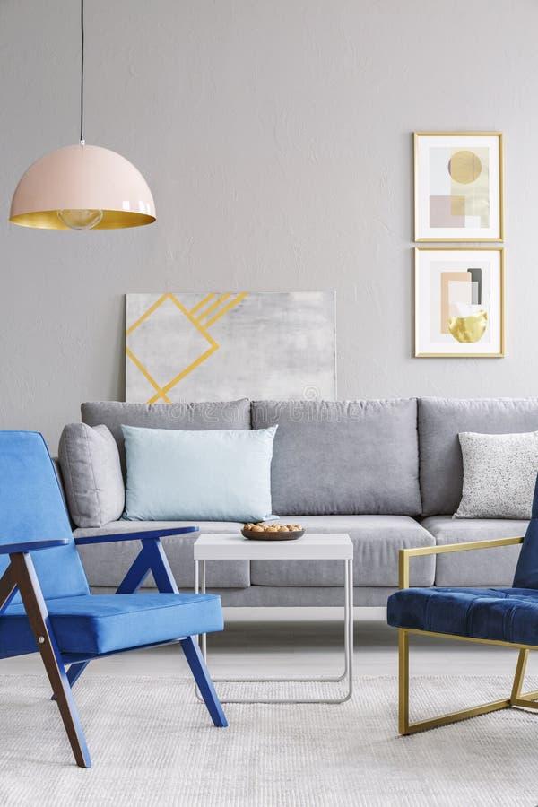 在白色桌和灰色沙发附近的蓝色扶手椅子在现代生活ro 库存照片