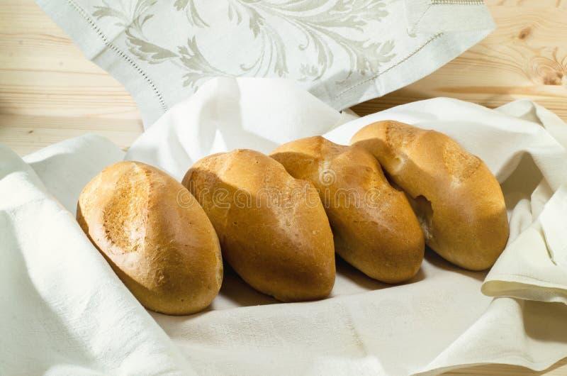 在白色桌布的新鲜面包在木桌上 面包店概念 免版税库存图片