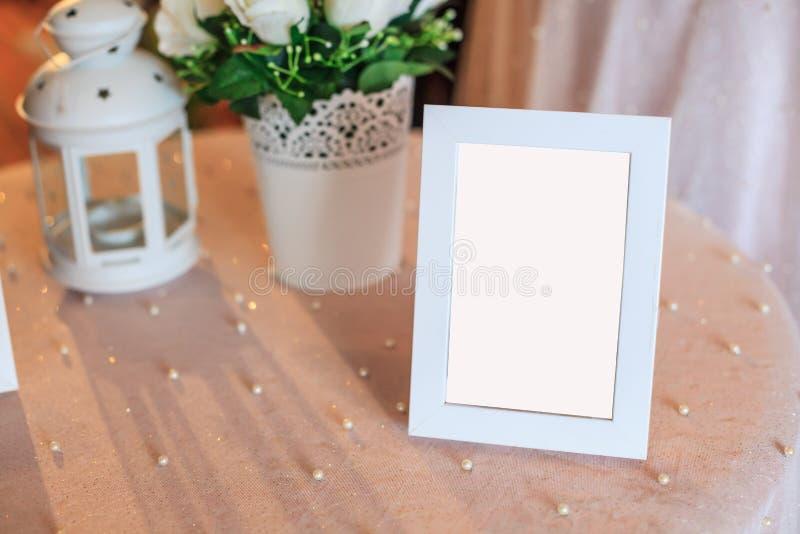 在白色桌布装饰的桌上的空白的木画框装饰 结婚宴会仪式,周年庆祝 免版税库存照片