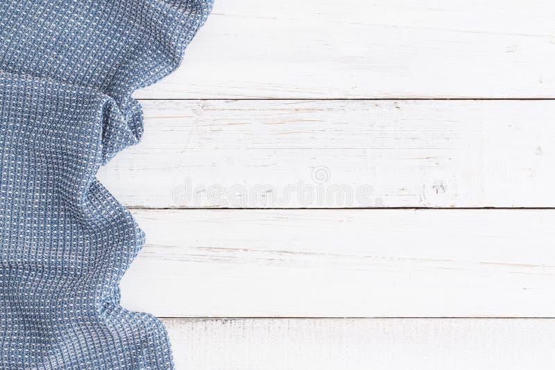 在白色桌木头、顶视图和拷贝空间的桌布蓝色为 免版税图库摄影