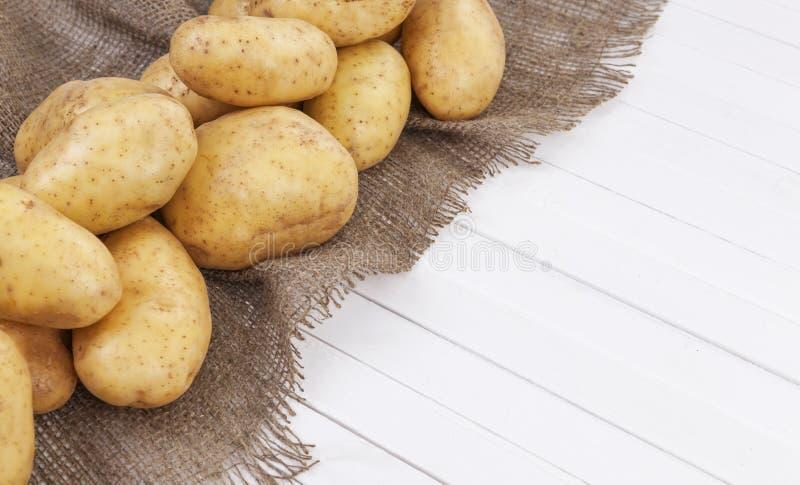 在白色桌背景隔绝的未加工的土豆 库存照片