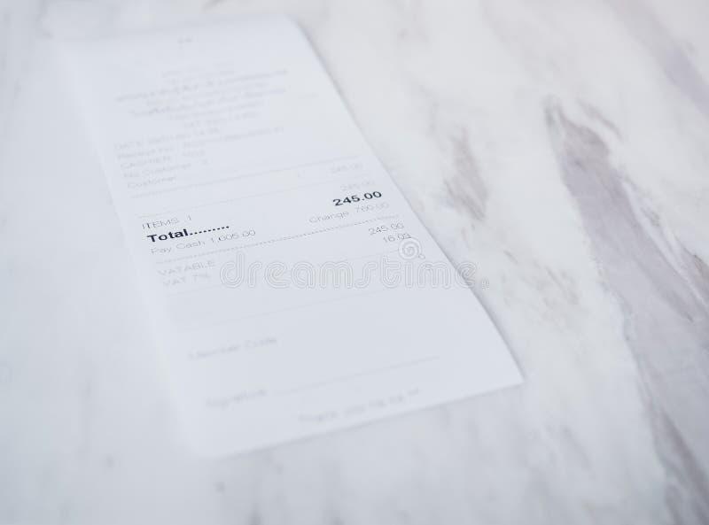 在白色桌顾客付款的收据 库存照片