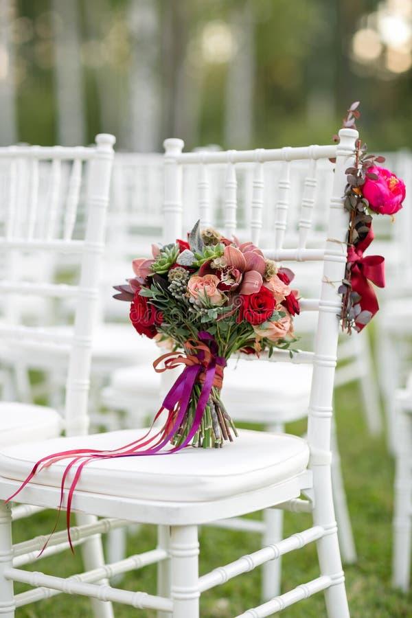 在白色椅子的惊人的红色新娘花束 新娘仪式花婚礼 多汁植物、兰花和玫瑰的混合 免版税库存图片