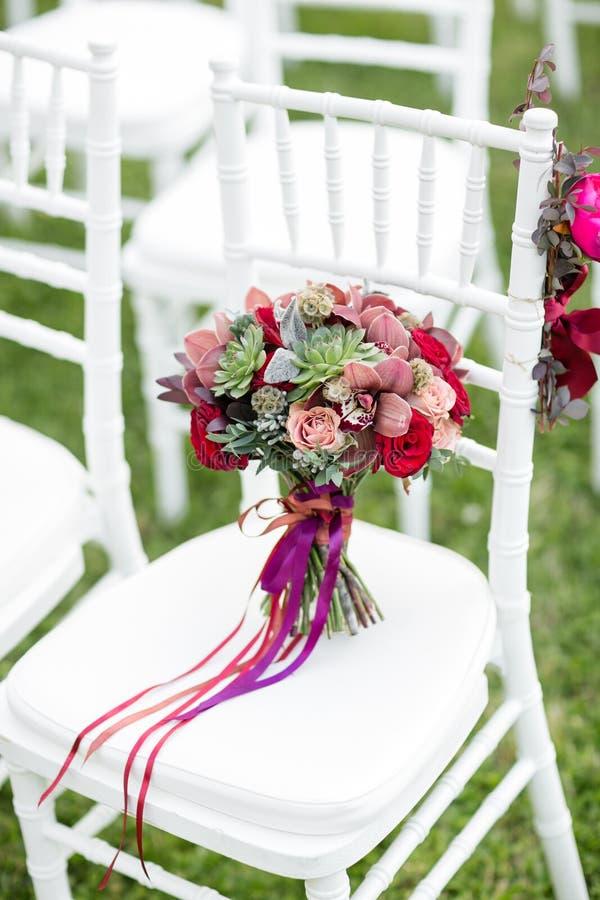 在白色椅子的惊人的红色新娘花束 新娘仪式花婚礼 多汁植物、兰花和玫瑰的混合 免版税图库摄影