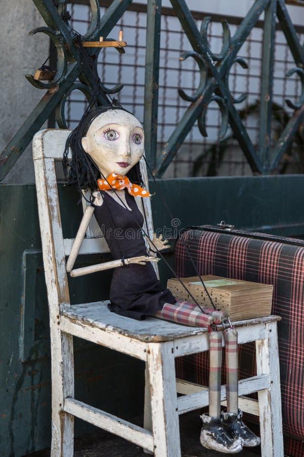 在白色椅子的木破旧妇女牵线木偶 库存图片