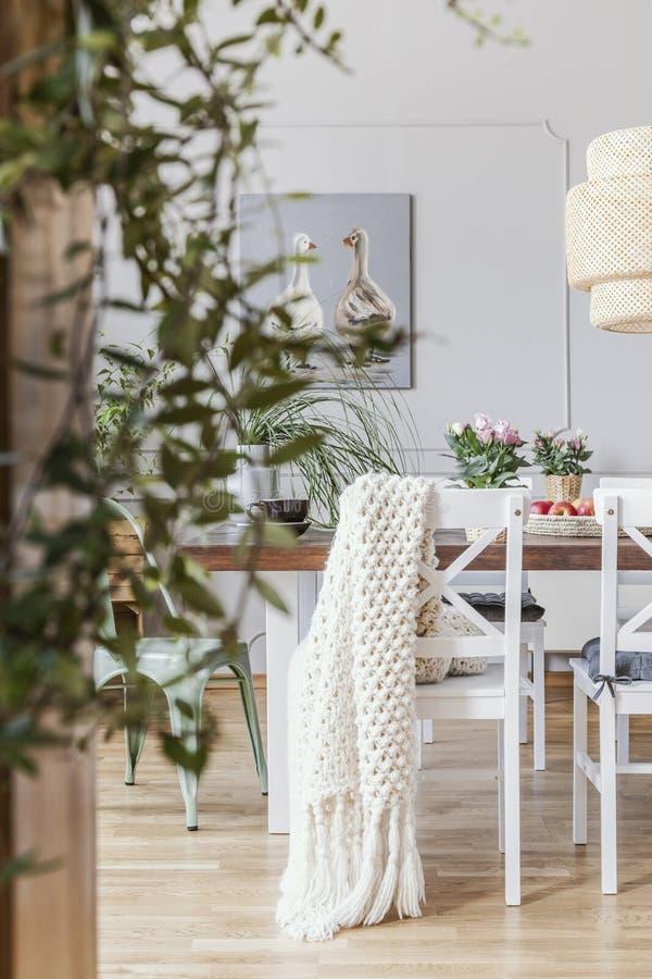 在白色椅子的毯子在餐厅内部的桌上与花和藤条灯 实际照片 免版税库存图片