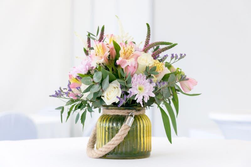 在白色欢乐桌上的美好的花的布置 库存照片
