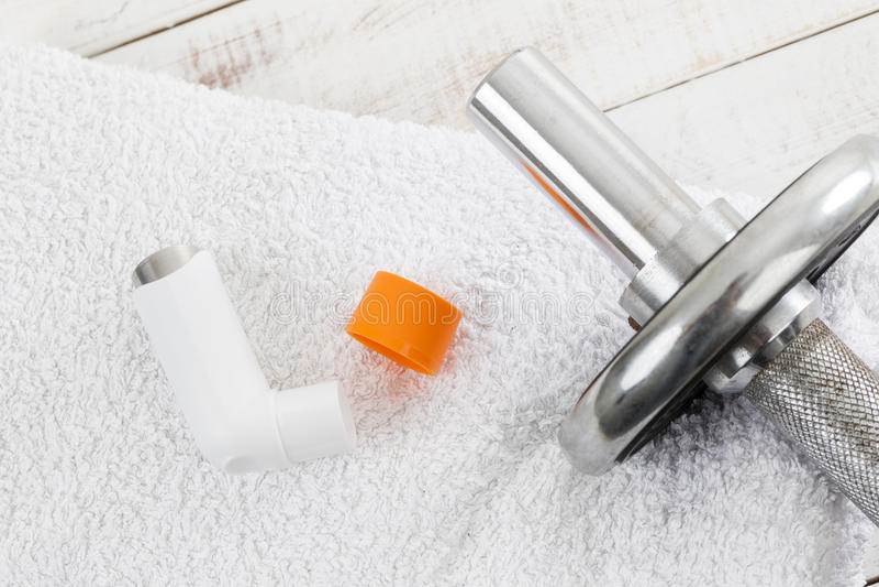 在白色毛巾的哑铃和哮喘吸入器 免版税库存图片