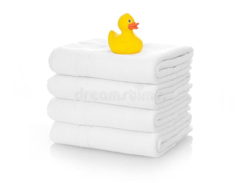 在白色毛巾的橡胶鸭子 免版税库存图片