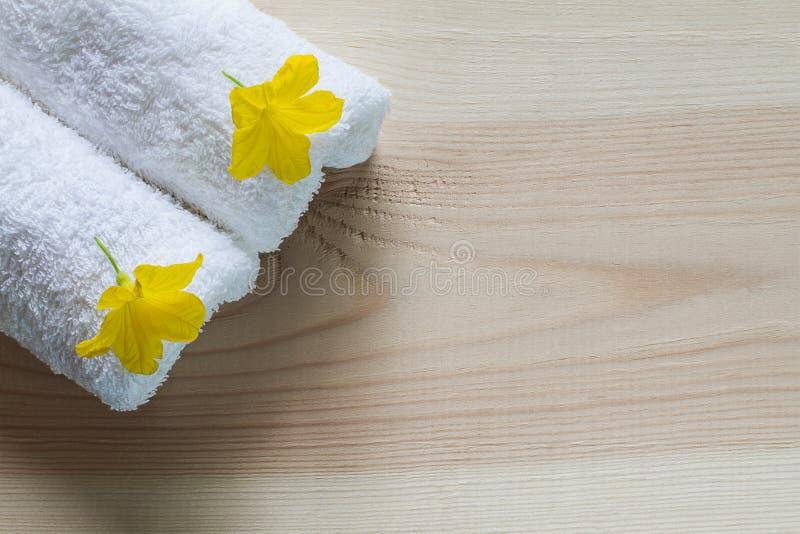 在白色毛巾的黄色花与在葡萄酒木背景的软的阴影 免版税库存图片