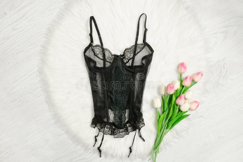 在白色毛皮的黑鞋带束腰 桃红色郁金香 时兴的概念 库存图片