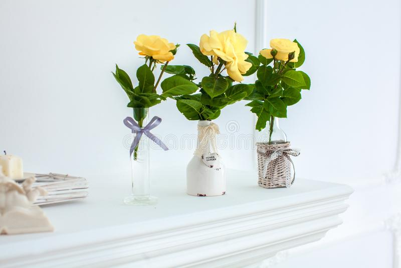 在白色水罐的黄色玫瑰在反对中立背景的白色桌上 免版税库存照片