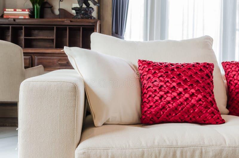 在白色沙发的红色和白色枕头在家 库存图片
