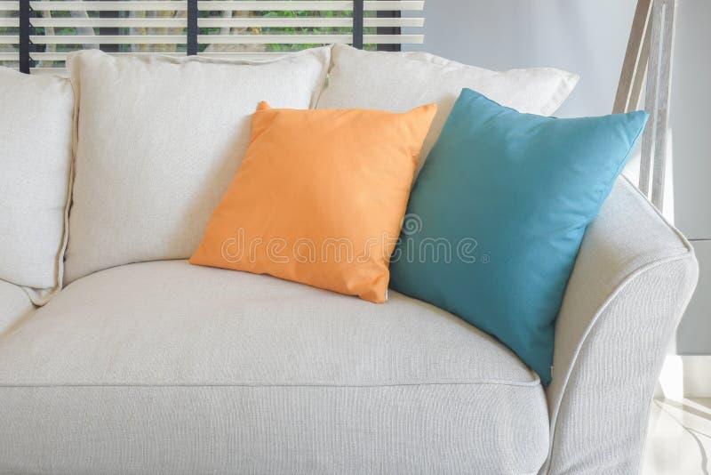 在白色沙发集合的黄色和绿色枕头 库存图片