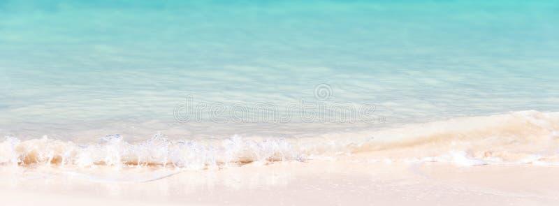 在白色沙子和绿松石的波浪浇灌,全景背景 图库摄影