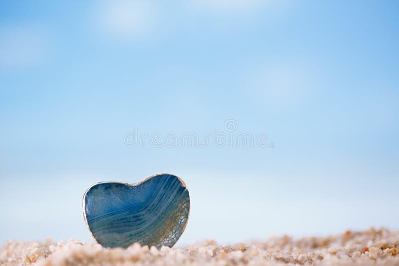 在白色沙子海滩的绿色宝石心脏 免版税库存照片