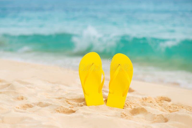 在白色沙子海滩的黄色凉鞋触发器有蓝色海和天空背景在暑假复制空间 免版税库存图片